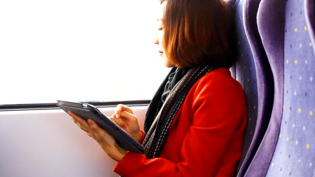 HD:Asian woman play tablet on the train. video