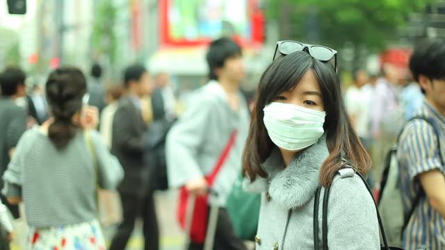 hd:asian woman wearing a mask standing in a big city. - maske stok videoları ve detay görüntü çekimi