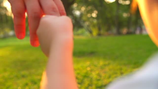 HD: bebé niño que toma de la mano a su madre en el parque. - vídeo