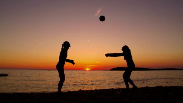 HD: Schöne Frauen spielen Sie Volleyball am Strand bei Sonnenuntergang – Video