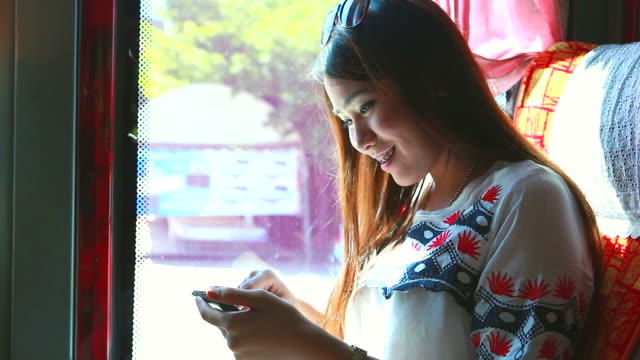 HD:Beauty asian women typing message on the bus. video