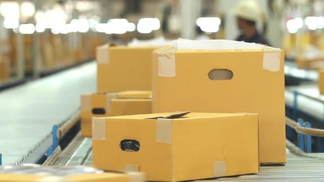 hd:carton box moving on conveyor rollers. - 2015 bildbanksvideor och videomaterial från bakom kulisserna