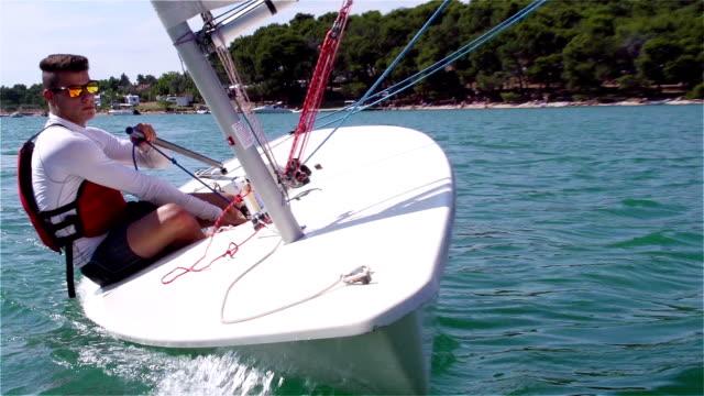 HD-Handheld: Shot of Young Man Sailing on Laser Class Boat HD 1080p: Handheld shot of young boats-man leaning on lasser class boat using main sail, Adriatic sea, Europe mast sailing stock videos & royalty-free footage