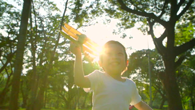 HD:Happy child playing wooden airplane in the park(Slow motion).. video