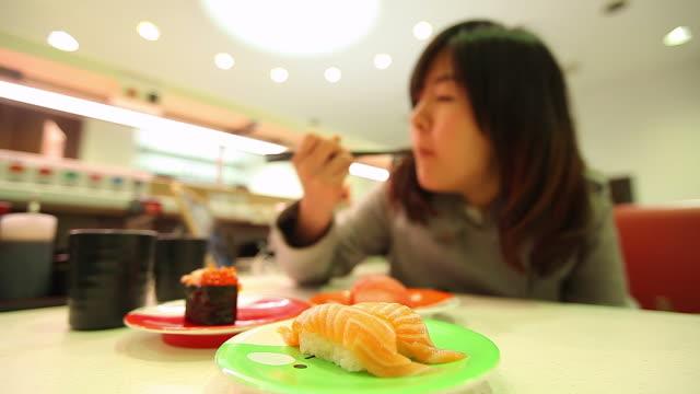 HD: japonés mujer comiendo en el restaurante sushi japonés. - vídeo