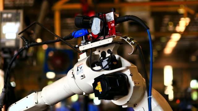 hd: articolazione del braccio robotico durante la saldatura. - metal robot in logistic factory video stock e b–roll