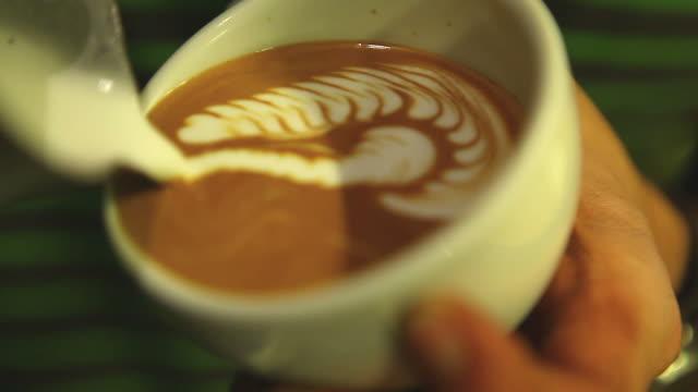 vídeos de stock, filmes e b-roll de hd: latte arte, leite que entra por um barista. - comida e bebida