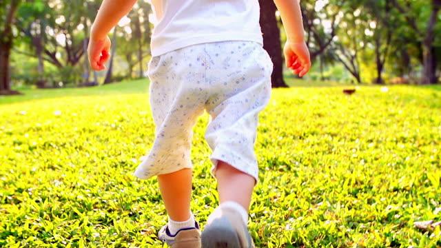 hd :  piccolo ragazzo corre in natura al parco con tramonto sfondo (al rallentatore - solo un bambino maschio video stock e b–roll