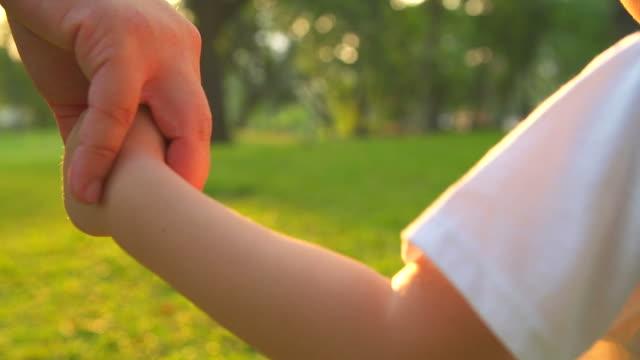 vídeos de stock, filmes e b-roll de hd: mãe e filho segurando lado e uma caminhada no parque. - mão humana
