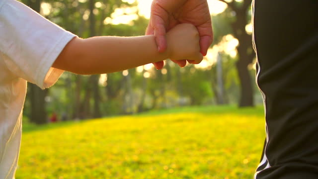 HD:Mother hold hand of his son walking in the park.