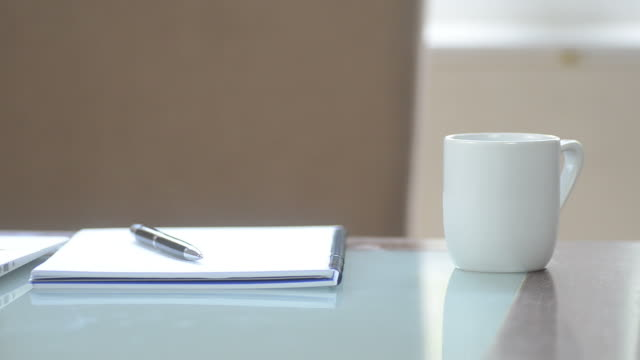 HD:Notebook and coffee cup on the desktop for relax and working video