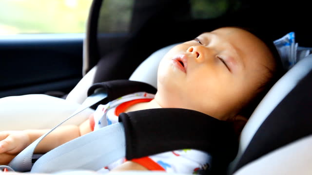 HD:Portrait of little baby  sleeping in safety carseat. video