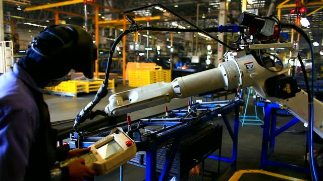 hd: braccio robotico saldatura durante il processo di strumento. - metal robot in logistic factory video stock e b–roll