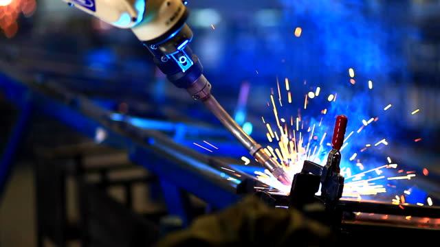 HD:robotic arm welding in factory.