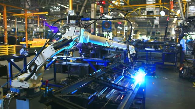 hd: braccio robotico saldatura. - metal robot in logistic factory video stock e b–roll