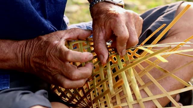 hd:senior hands manually weaving bamboo basket. - halmslöjd bildbanksvideor och videomaterial från bakom kulisserna