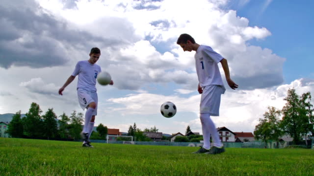 HD:Shot of two soccer players performing kick-ups video