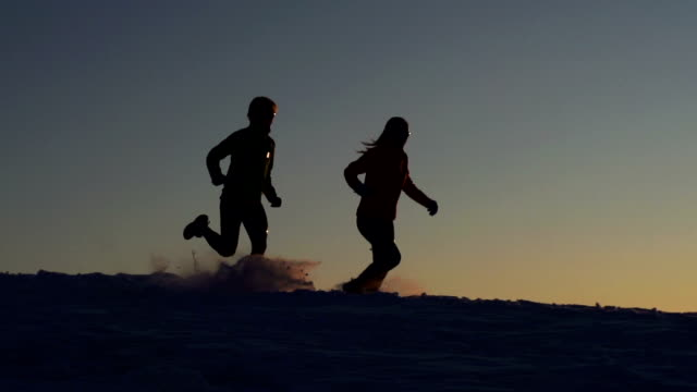 HD:Silhouette of young couple at snow running video