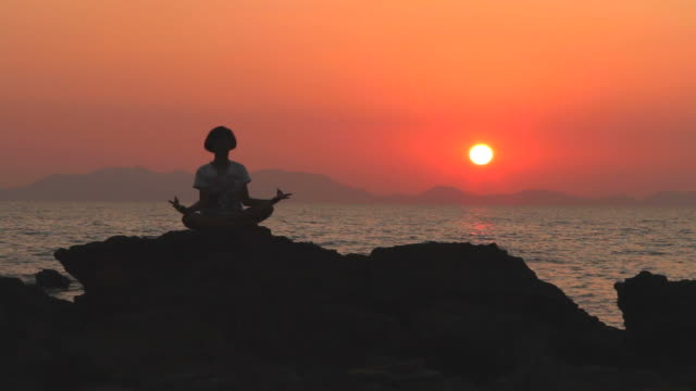 HD:Silhouette of young woman in yoga lotus meditation. video