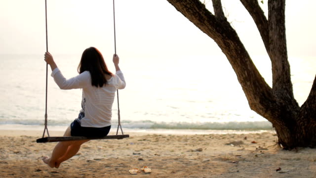 HD:Woman on swing on the beach with sea at sunset time , slow motion , relaxation concept video