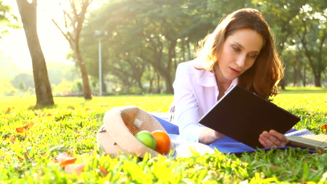 HD:Woman relaxing with tablet in the park. video