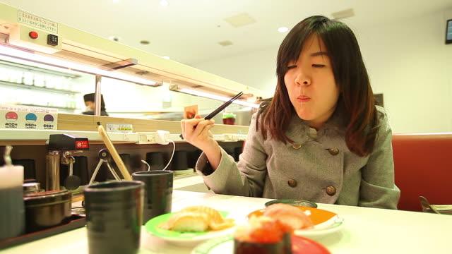 HD :若い美しい女性の寿司を食べるアジアの箸 ビデオ