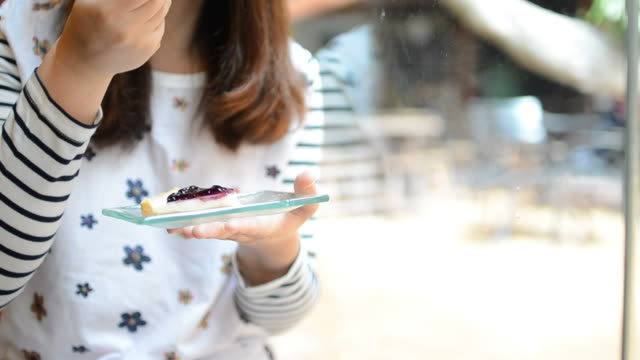 HD:Young woman eating blueberry cheese pie cake