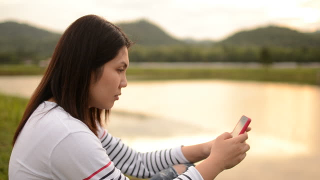 HD:Young woman touching smartphone in nature video