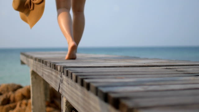 HD:Young woman walking on the wooden bridge near the sea in relaxing summer time , slow motion