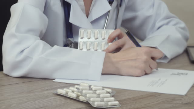he doctor looks at tablets and writes a prescription video