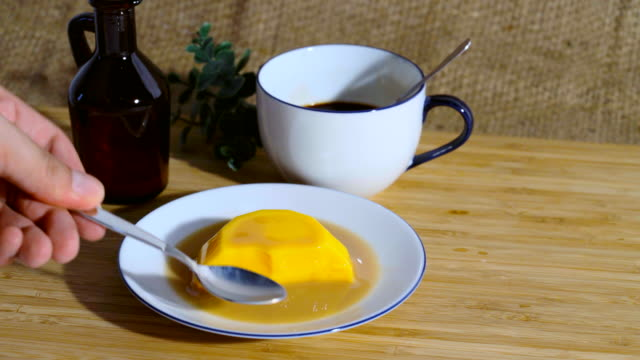 He poured tea into pudding in a bowl. On a wooden table with coffee mugs nearby, 4k 30fps resolution. video