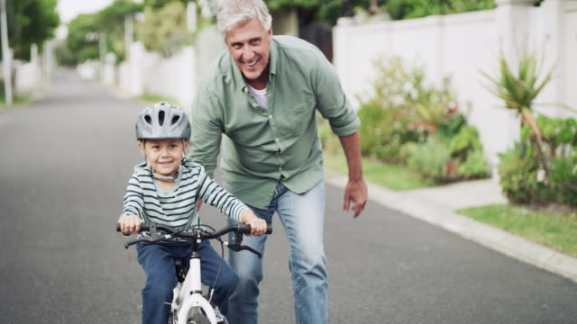 He was born to ride 4k video footage of an adorable little boy getting taught how to ride a bicycle by his grandfather outdoors granddaughter stock videos & royalty-free footage