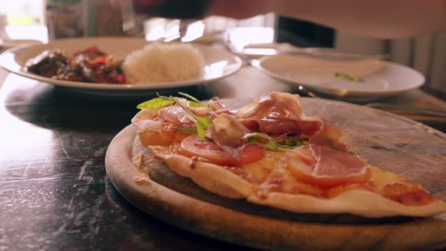 stockvideo's en b-roll-footage met hij was plukken pizza parma ham uit de houten pan en een glas cola aan de zijkant. - dikke pizza close up