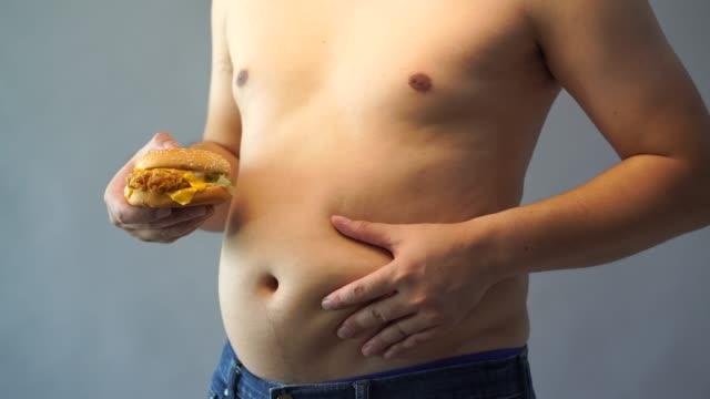 vídeos de stock, filmes e b-roll de ele se preocupava com a obesidade, a mão segurando um hamburguer. - junk food