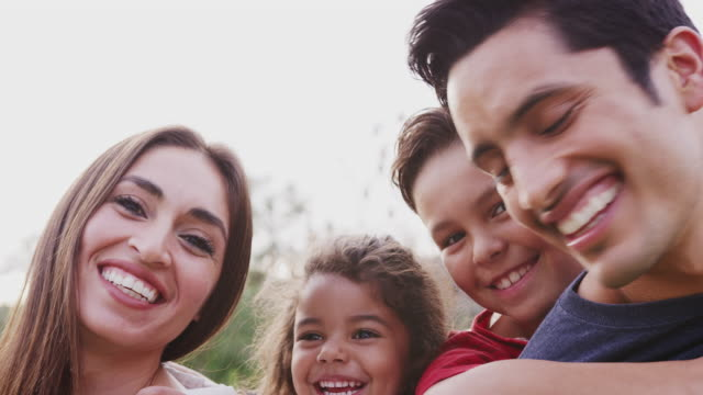 Head and shoulders close up of smiling young Hispanic parents piggybacking their children in park Head and shoulders close up of smiling young Hispanic parents piggybacking their children in park sister stock videos & royalty-free footage