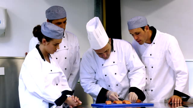 Head chef showing his trainees how to fillet a salmon video