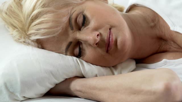 躺在枕頭上的高級婦女的頭, 輕的微笑在她的面孔, 未受干擾的睡眠 - 深的 個影片檔及 b 捲影像