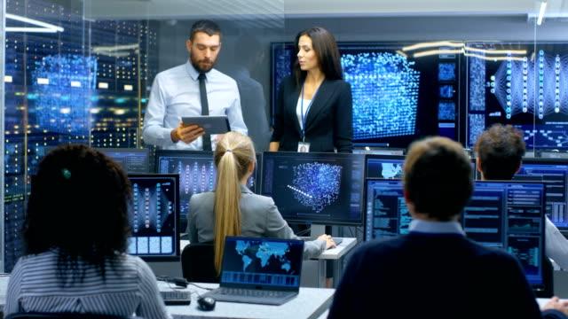 Chef du département et Project Manager discuter travail processus à l'aide de données sur une tablette Computer.Multi-Ethnic équipe des ingénieurs qui travaillent dans leurs Workstation.Displays Show travail modèle de réseau neuronal - Vidéo