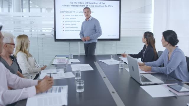 会議室の大型スクリーンを使用してウイルスのアニメーション プレゼンテーションを与える医療チームの頭 - レポートのビデオ点の映像素材/bロール