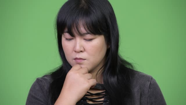 Head shot of serious overweight Asian woman thinking video