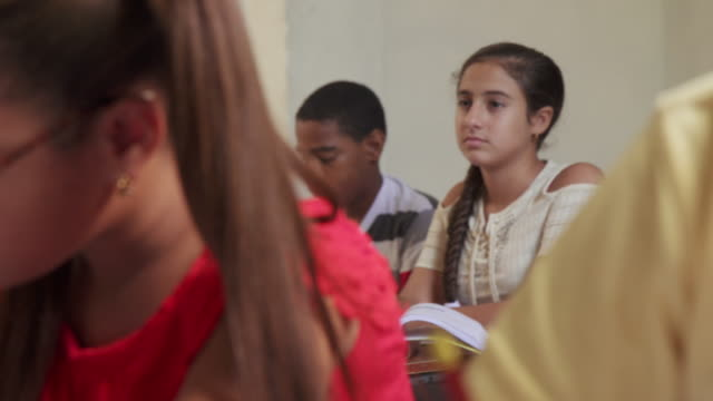 Headache For Sick Stressed Student Girl In Class At School Young people and education. Group of hispanic students in class at school during lesson. Girl with headache, sick female student middle school teacher stock videos & royalty-free footage