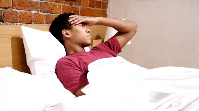 Headache, Tense African Man with Stress, Relaxing in Bed video