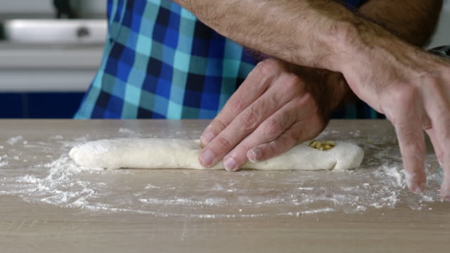 vídeos de stock e filmes b-roll de headless torso of a man making a small loaf of bread with nuts - baking bread at home