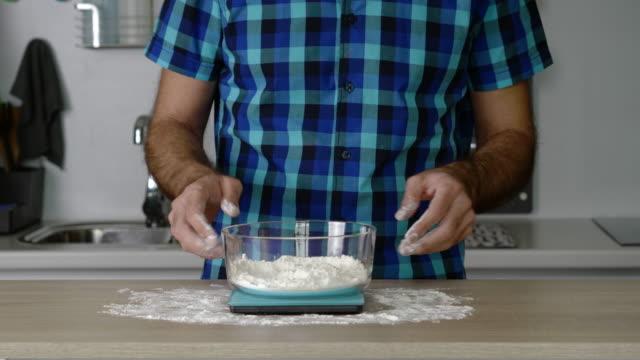 vídeos de stock e filmes b-roll de headless torso of a man weighing flour on a small digital scale - baking bread at home