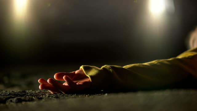 fari illuminano luogo di brutale omicidio, vittima senza vita sdraiata su strada - cadavere video stock e b–roll