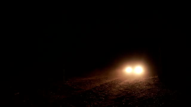 Headlights of car approaching on a dark road