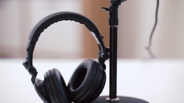 vídeos de stock, filmes e b-roll de auscultadores e microfone no escritório home - podcast
