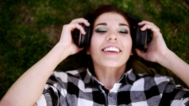 Headphones in the female hands. Charming girl lying on her back on the grass, putting on headphones and listening with pleasure to music. Shooting from the top