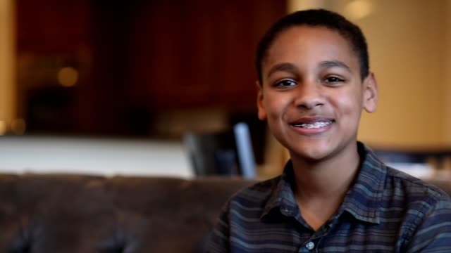 Headshot of African descent teenage boy at home. video