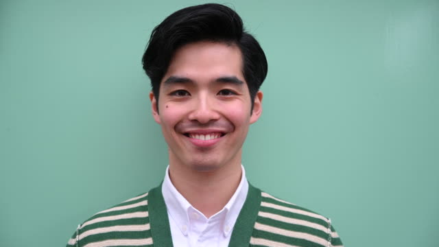 Headshot portrait of a young Japanese man smiling Asian male in twenties portrait on plain green background background color stock videos & royalty-free footage